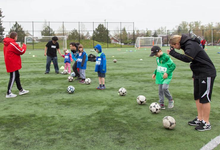 A group of children line up for a soccer activity in an outdoor field under the direction of their coaches.