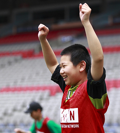 A child with autism holding his hands up to cheer at our annual Sports Day event.