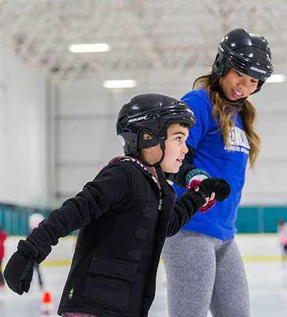 A child with autism ice skates while holding his support worker's hand in our I CAN Skate program.