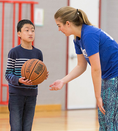 A child with autism plays basketball with the support of a staff member in our I CAN Play Sports program.