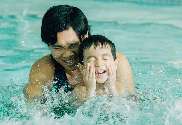 A child with autism and his support worker splash in the water together at our I CAN Swim program.