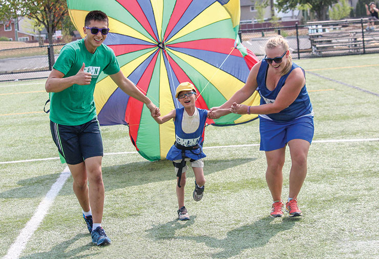 A volunteer and a staff member support a child with autism together in our Multisport summer day camp program.
