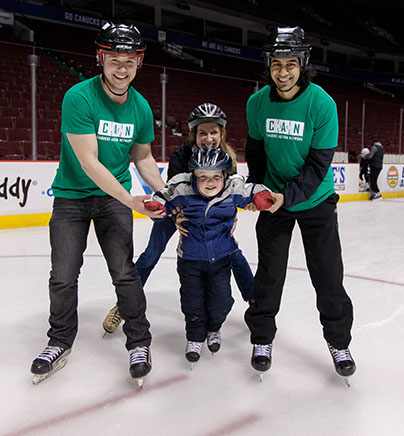 Two volunteers and a parent support a child with autism on the ice during our Rogers Arena Family Skate.