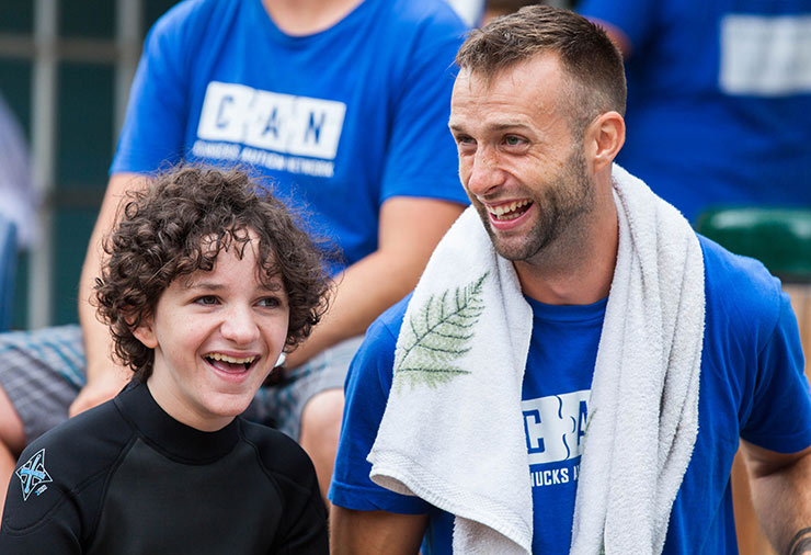 A child with autism and his support worker laughing together in our Overnight Camp program.