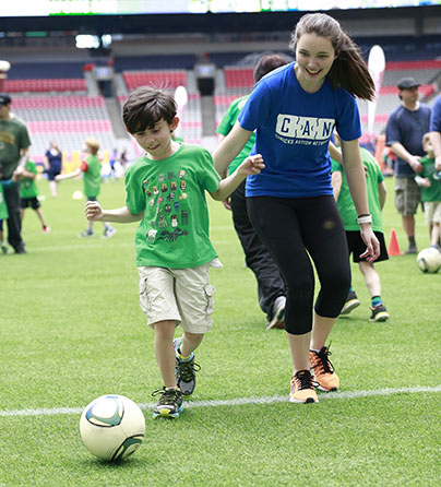 A child with autism dribbles a soccer ball with a support worker at our Sports Day event.