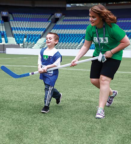 A child with autism and a volunteer run together with a hockey stick at our annual Sports Day.