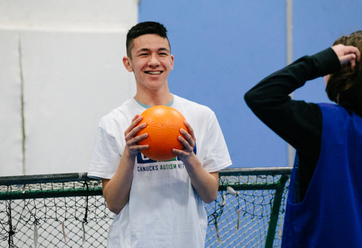 An youth on the autism spectrum holds a ball in a gym setting