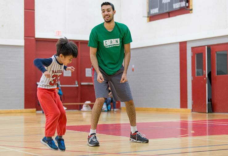 A volunteer and a child with autism jump together in our I CAN Be Active program.