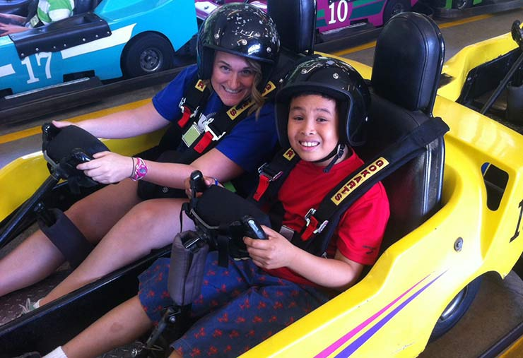 A support worker and a child with autism go-karting together in our Monthly Social Program.