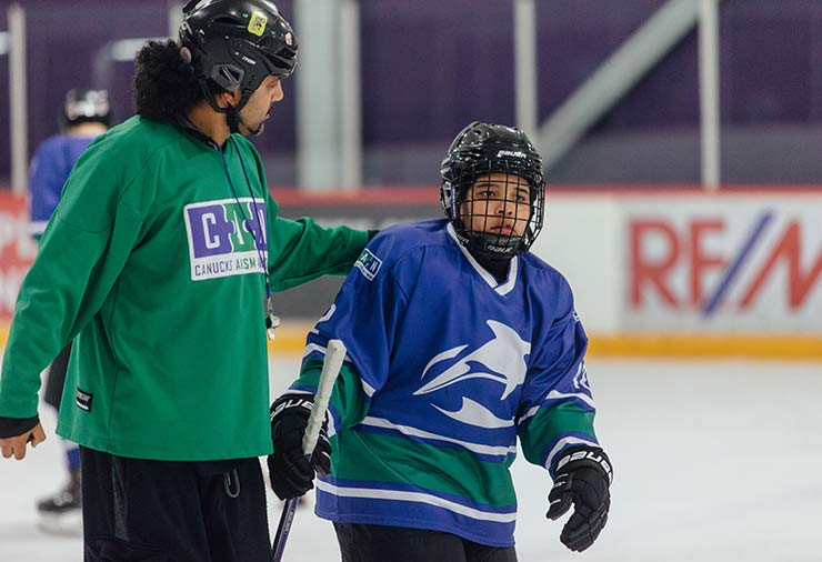 A coach and a child with autism on the ice together in our hockey program