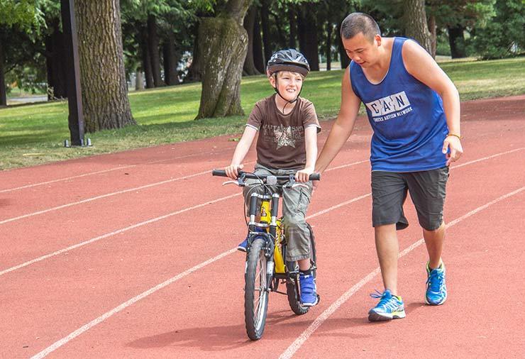 A coach supports a child with autism on his bike.