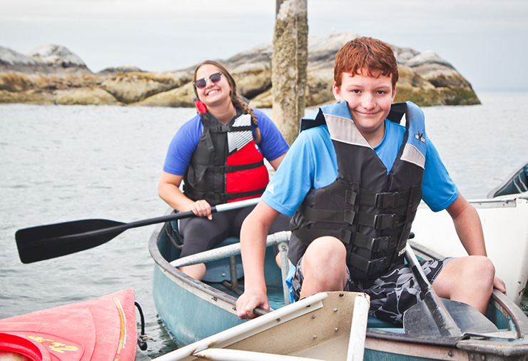 A child with autism and his support worker pose in a canoe together in our Overnight Camp program.