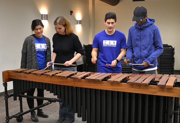 Support workers and teens with autism play a xylophone together in our Sarah McLachlan School of Music program.