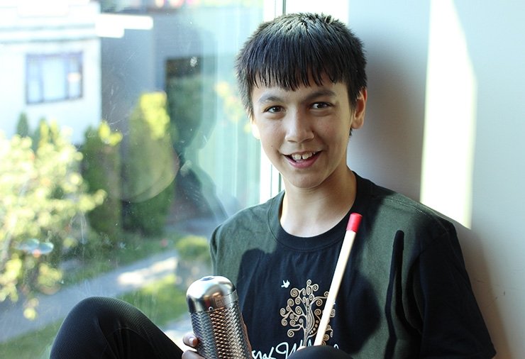 A teenager with autism poses with his instruments in our Sarah McLachlan School of Music program.