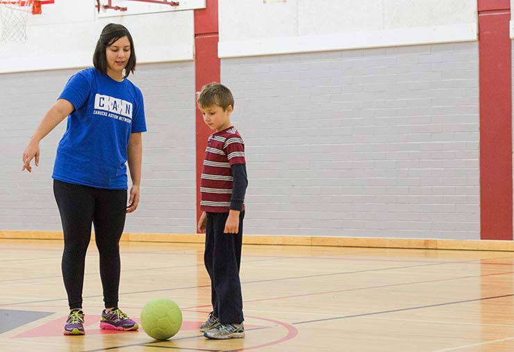 A support worker instructing soccer to a child with autism in our I CAN Play Sports program.
