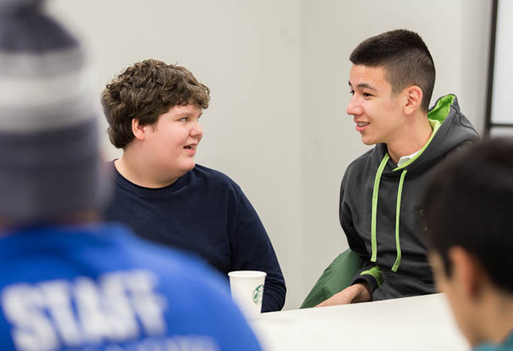 Two teens with autism talk with one another in our Weekly Social Program.