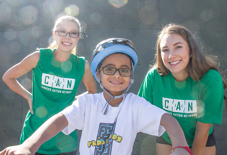 Volunteers pose with a child with autism in our I CAN Bike program.