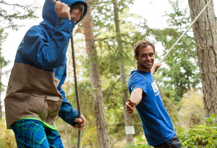 Support worker reaches out to a child with autism on ropes course at overnight camp program