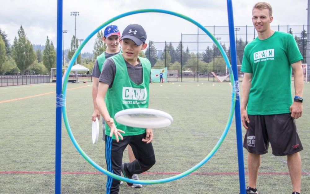 A child with autism throws a flying disc through a hoop under the guidance of a male volunteer.