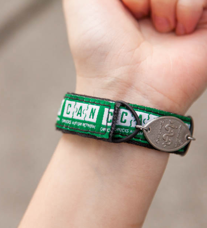 A green MedicAlert Canucks Autism Network bracelet worn on an individual's wrist
