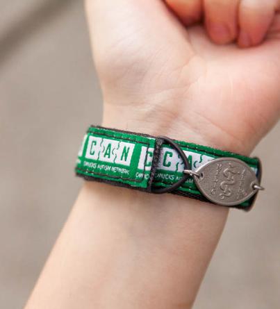 A green MedicAlert Canucks Autism Network bracelet worn on an individual's wrist