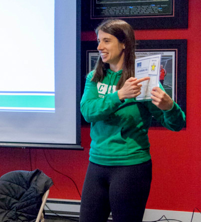 A woman presents in front of a classroom as part of an autism training workshop.