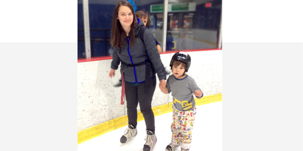 A mother skates on the ice while holding her son's hand.