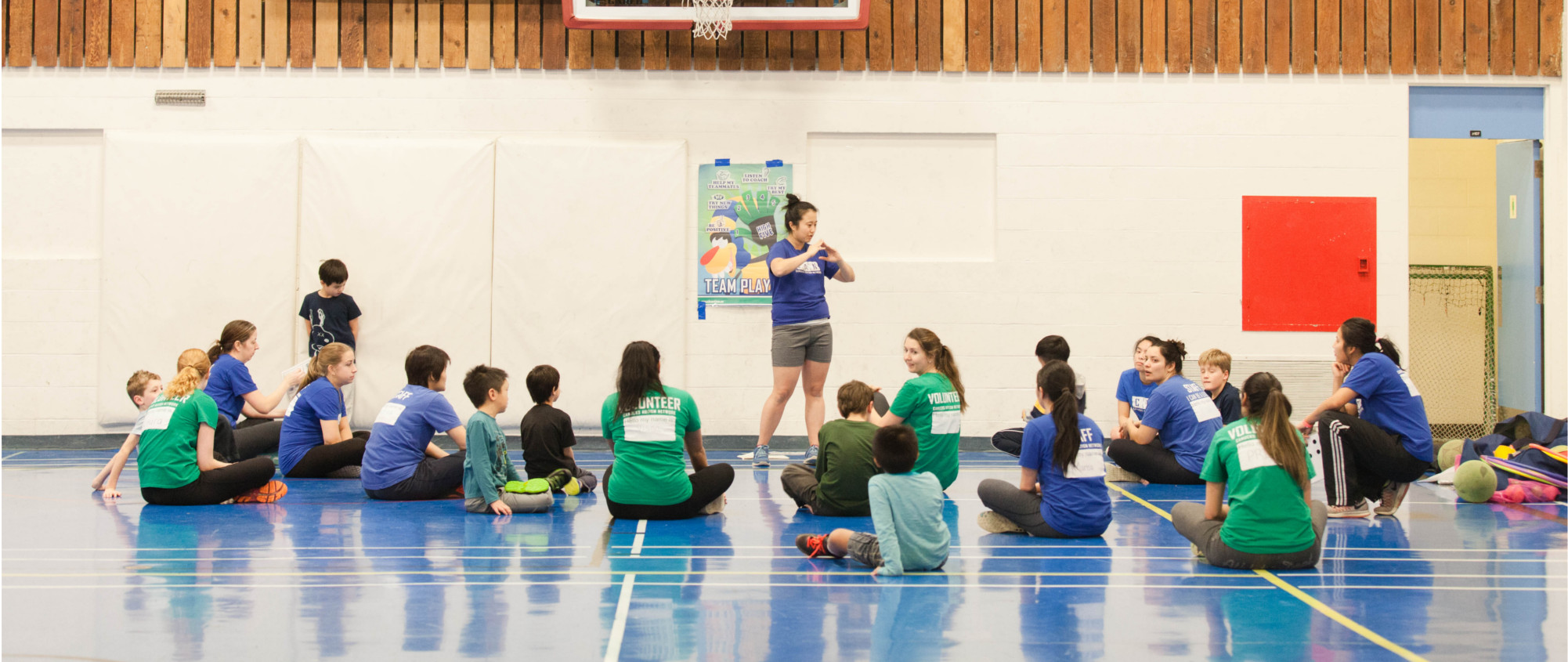 A coach stands in front of seated staff, volunteers and participants within a sports program.