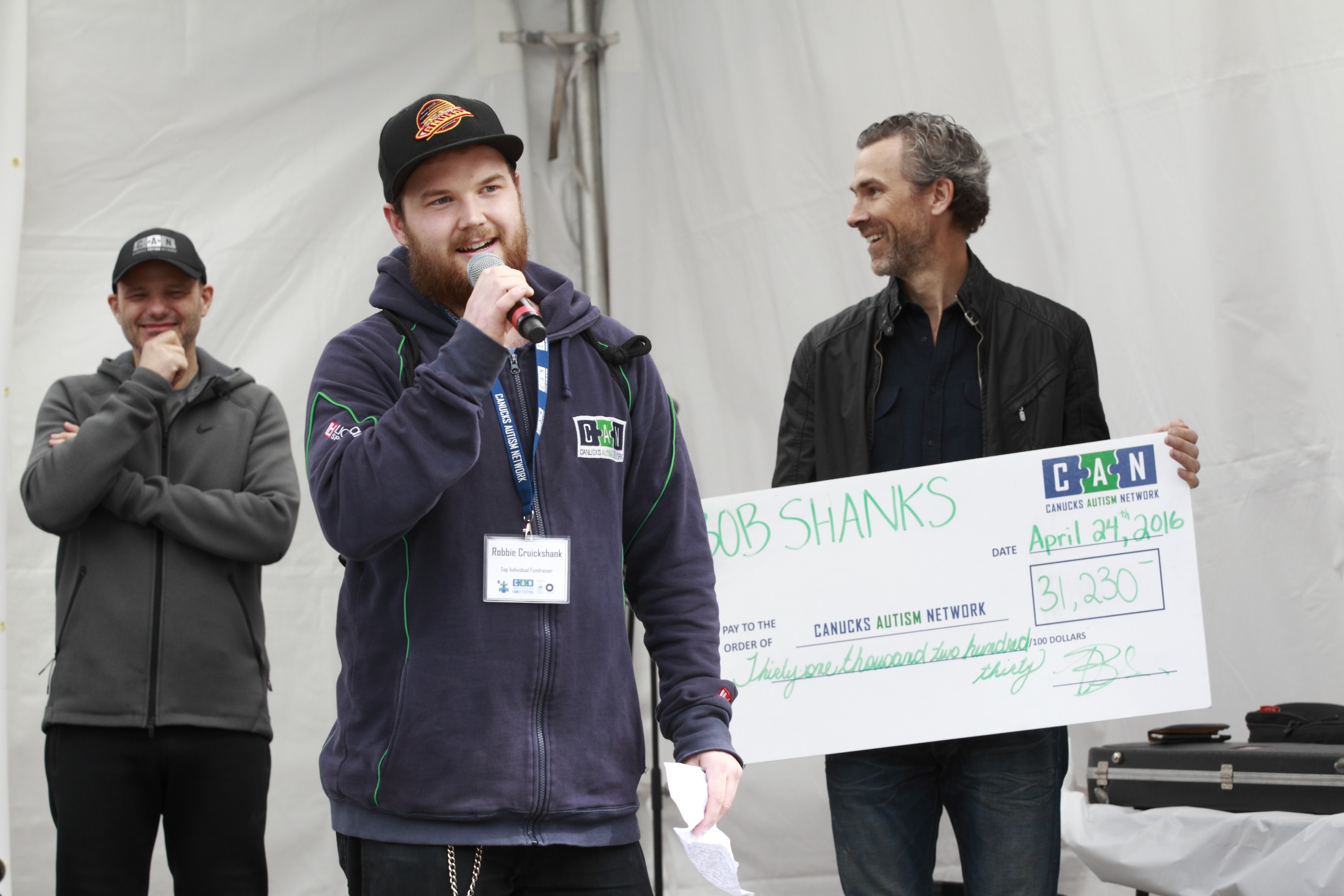 A young man speaks with a microphone with two men standing behind him holding a giant cheque.