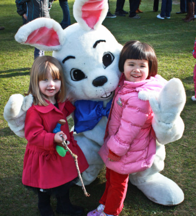 A costumed Easter bunny poses for a photo with two young girls.