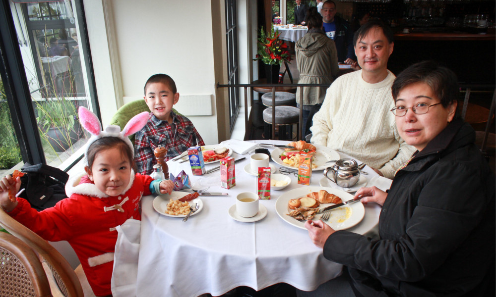 A family poses for a photo while seated around a restaurant dinner table.