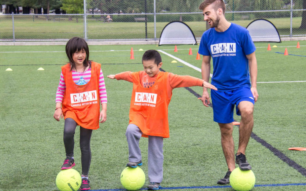 A female child, a male child and an adult male stand in a row on an outdoor turf field, each with a soccer ball under one of their feet.