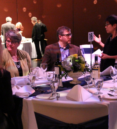 Guests at a fundraising gala are seated around a dinner table.