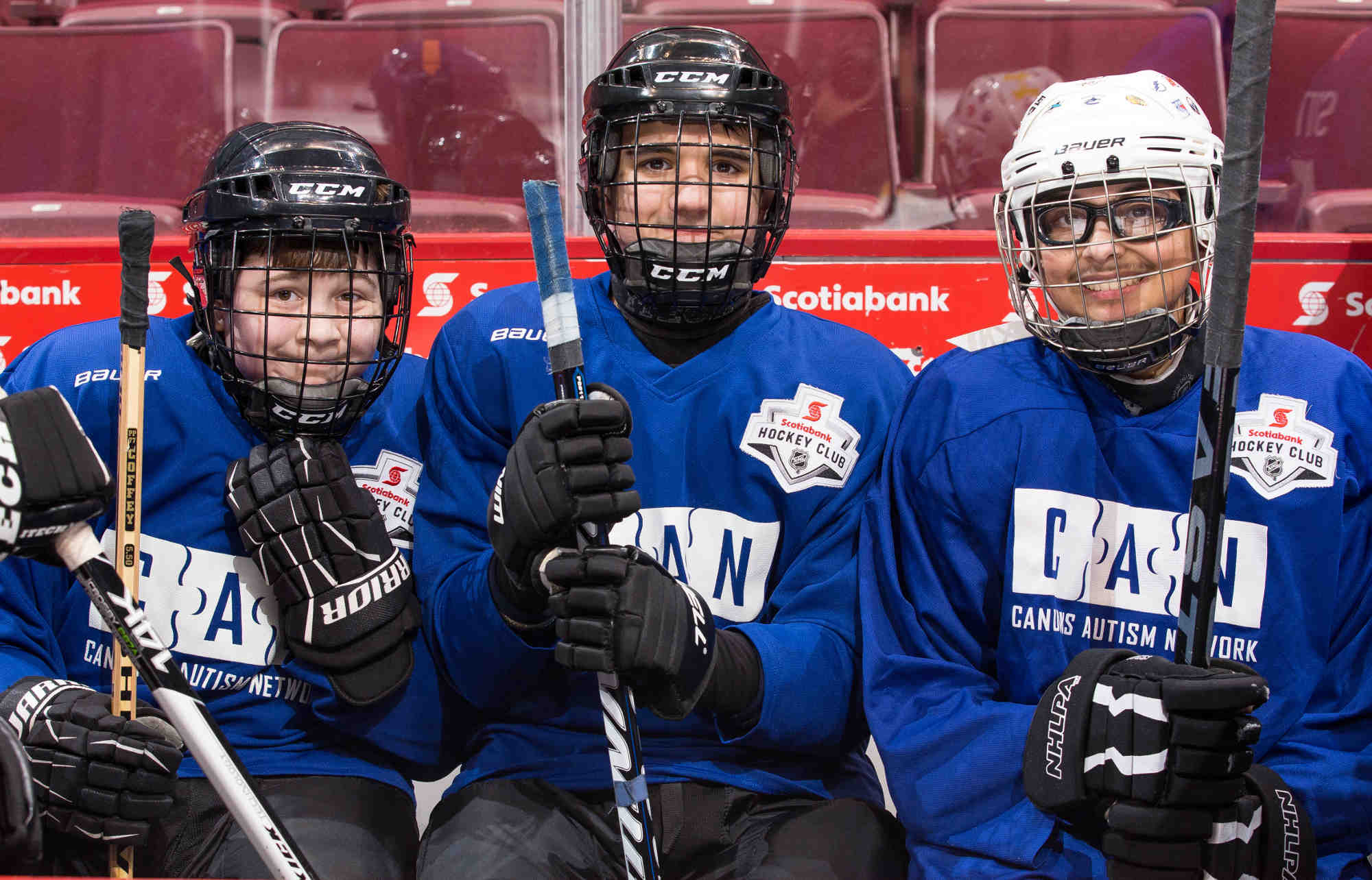 Three male youth hockey players pose for a photo while sitting on a bench together.
