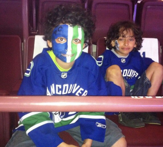 Two young boys wearing hockey jerseys, one of which has his face painted, sit in the stands at Rogers Arena during a hockey game.