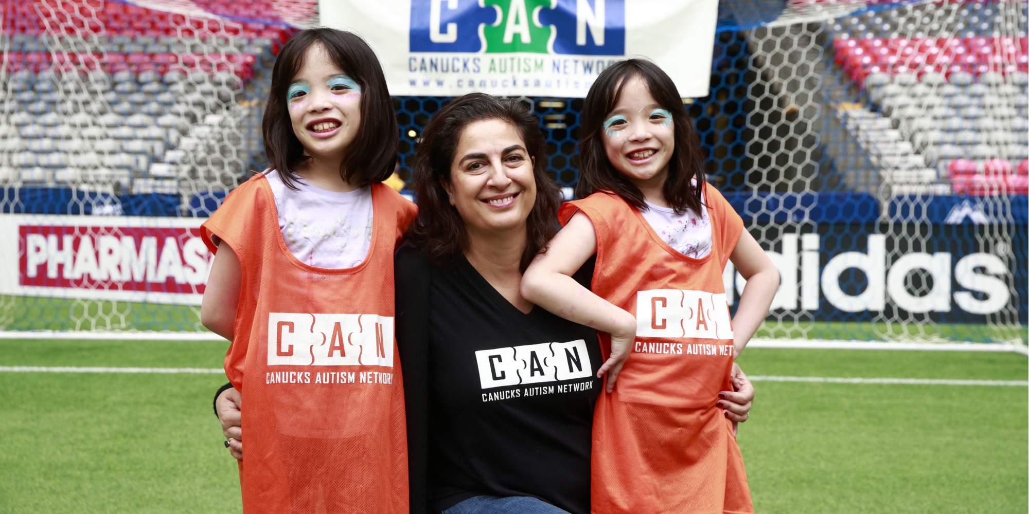 A woman with two twin girls poses for a photo.