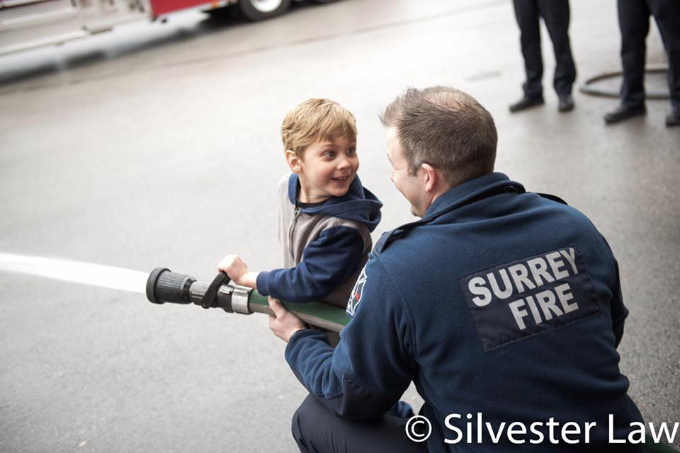 A child and a fire fighters hold a fire hose together, while the child looks back at the firefighter and smiles.