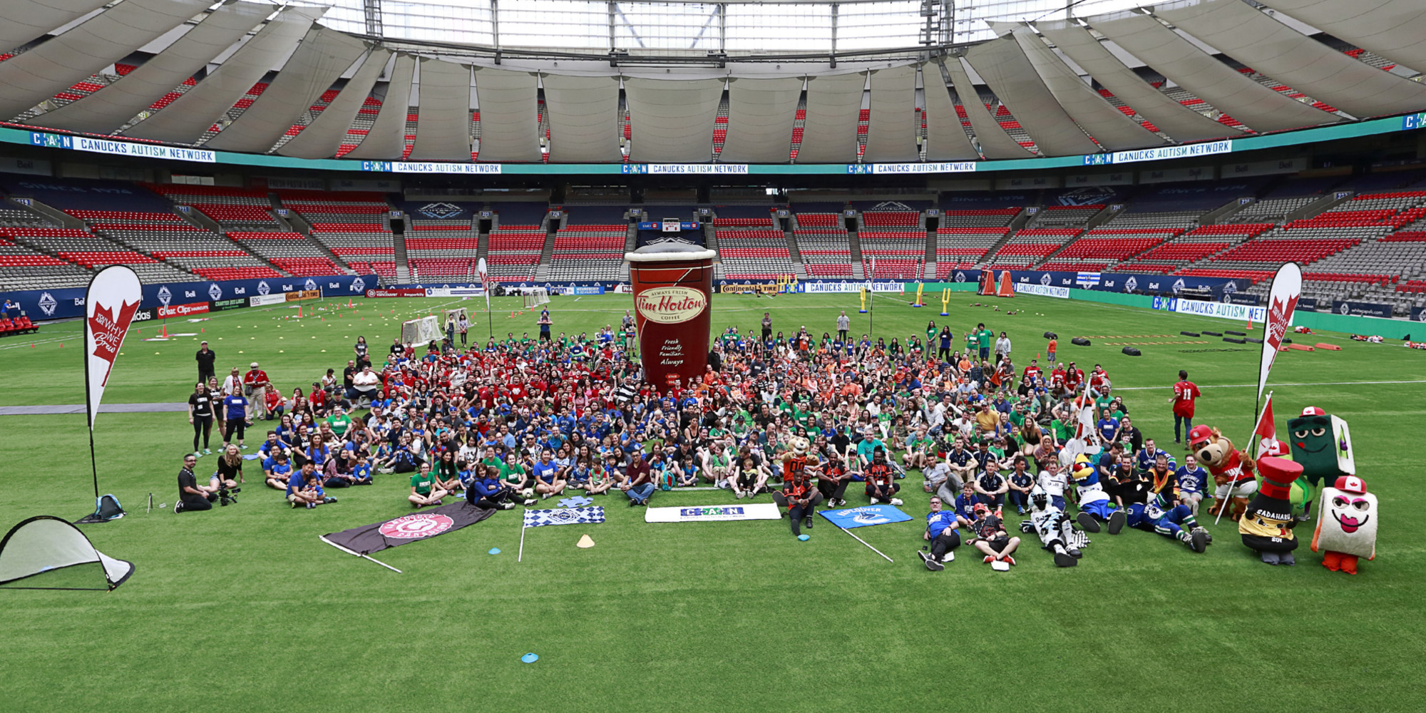 A group of 300+ families, staff, volunteers and professional athletes pose for a photo on-field at a sports stadium.