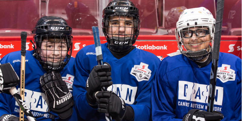 Three young hockey players sitting on the bench.