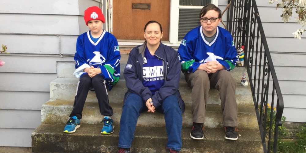 A mother and her two boys sit on their front porch steps wearing hockey jerseys.
