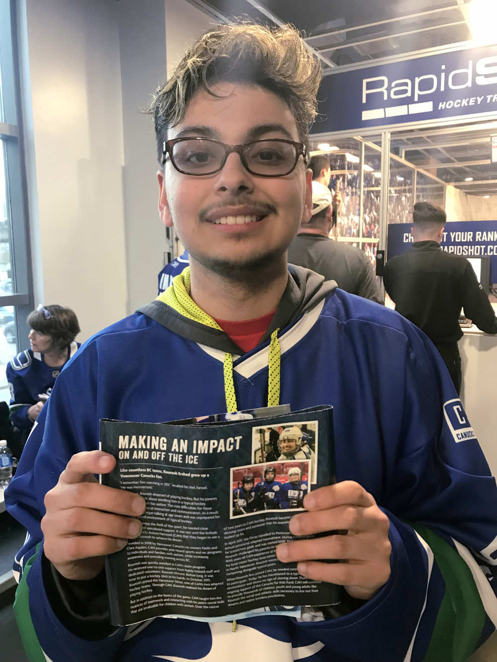 A teen male poses for a photo in an arena concourse holding a game-day magazine.