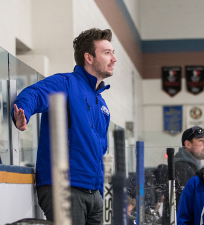 A male hockey coach stands on an arena bench.