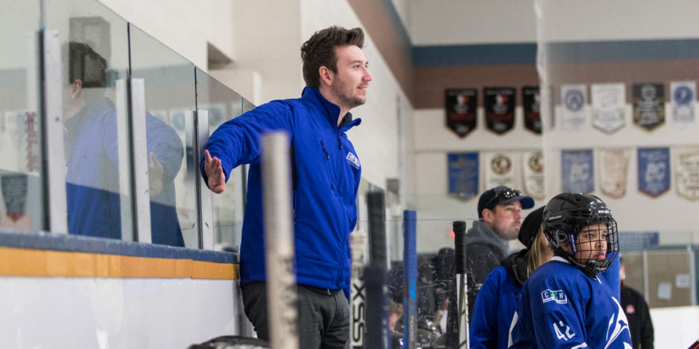 A male hockey coach stands on an arena bench behind youth hockey players during a game.