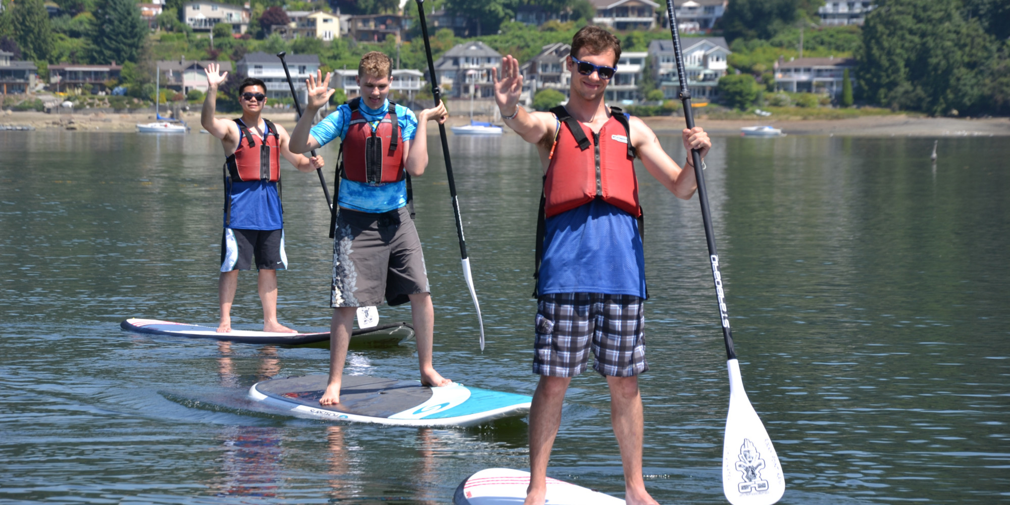 Three young men wave to the camera while standing on paddle boards.