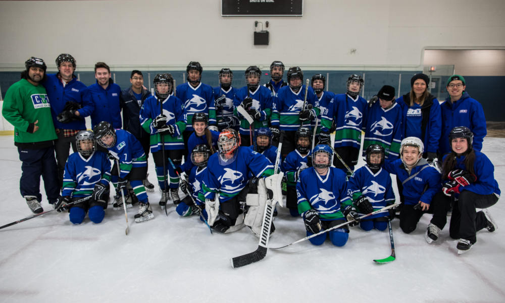 A youth hockey team and their coaches pose for a team photo.
