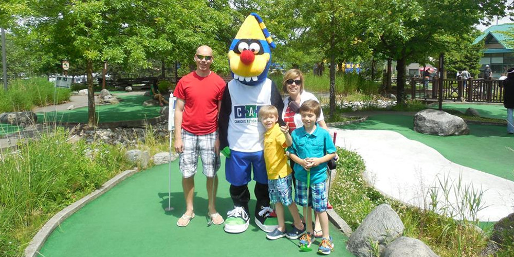 A family of four pose for a photo with a mascot on a mini golf course.