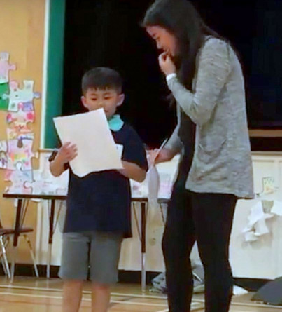 A young boy recites a poem while his older sister watches beside him.