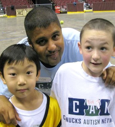 Two boys pose for a photo with their coach.
