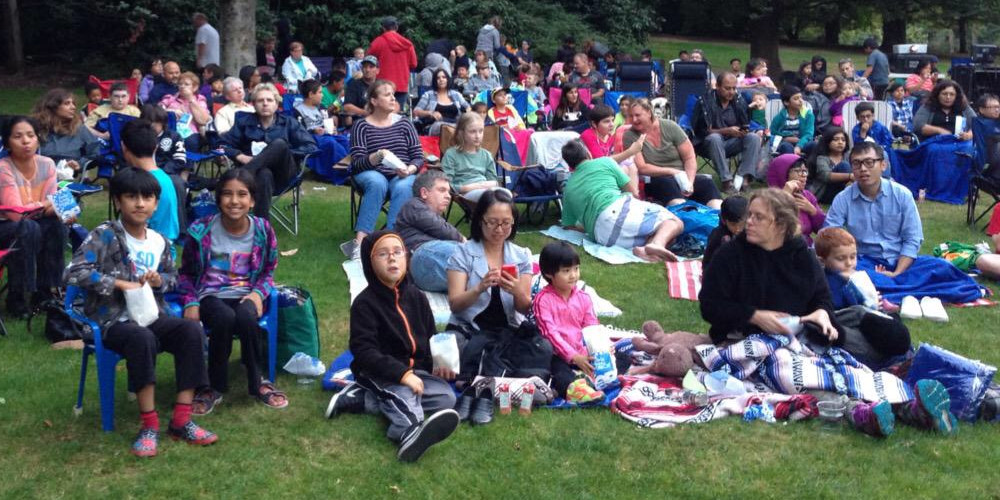 A group of roughly 100 families sit on blankets in the park.
