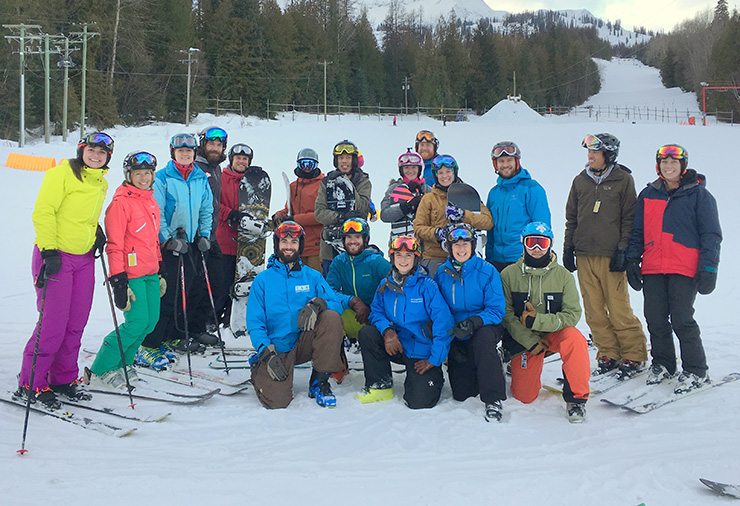 A group of adults wearing ski gear posed on a snowy mountain.